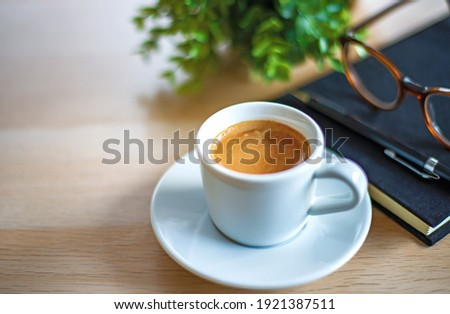 coffee break concept, close-up a cup of espresso coffee with black notebook , pencil and the glasses on white table. soft tone color picture