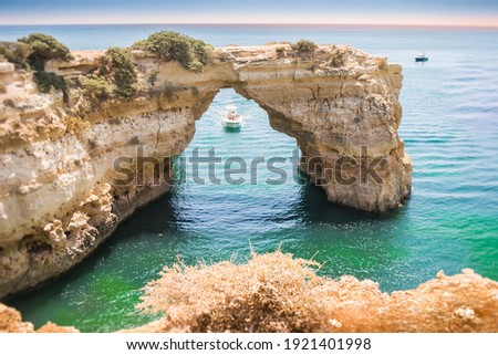 Coastal coastline with rocky arch at Albandeira beach in Algarve, Portugal Royalty-Free Stock Photo #1921401998