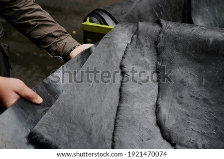One of the first stages of production of rubber products at the plant. Close-up of raw material seam texture. Medium wholesale manufacturing technology, Royalty-Free Stock Photo #1921470074