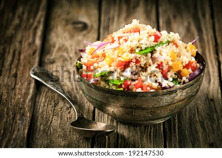 Healthy vegetarian quinoa recipe with colourful bell pepper, tomato, onion and fresh herbs in a rustic metal bowl on an old wooden kitchen counter Royalty-Free Stock Photo #192147530