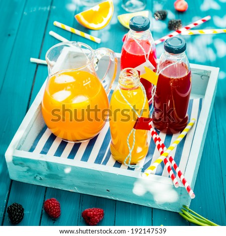 Bottles of freshly squeezed orange and berry juice standing on a wooden tray on a colorful turquoise blue picnic table in dappled summer sun