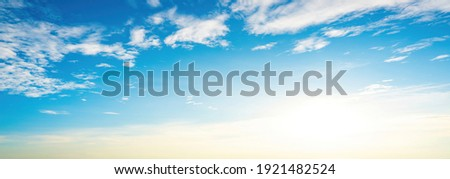 The sky has the light of the sun; the sky is blue; there are small and large clouds alternating and moving slowly; with the sunlight passing; creating a miraculous abstract shape; a hot day. Royalty-Free Stock Photo #1921482524