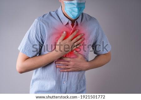 Man with coronavirus symptoms on gray background, studio shot Royalty-Free Stock Photo #1921501772