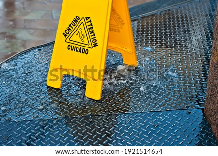 Yellow danger sign. Symbol of a slippery sidewalk. Inscription attention in different languages. Plate near the cobblestones in the spring. Royalty-Free Stock Photo #1921514654