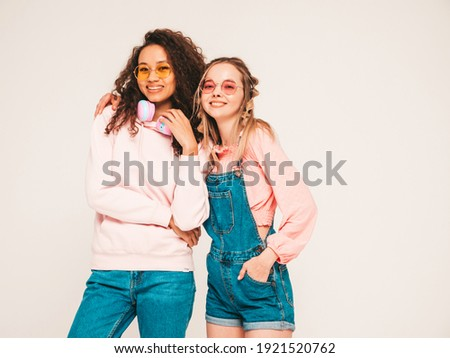 Two young beautiful smiling international hipster female in trendy summer clothes.Sexy carefree women posing on grey background in studio.Positive models having fun in sunglasses.Concept of friendship