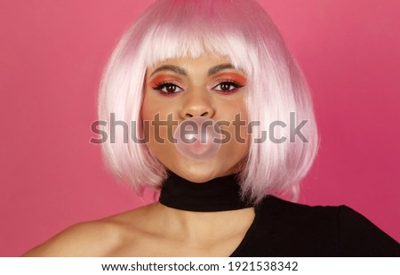 Photo of good looking young African American female with vivid make up inflates a bubble of gum  on a pink background.
