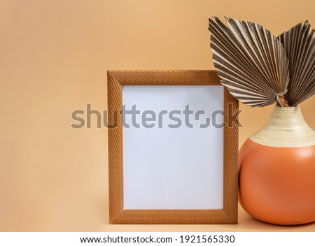 Modern round vase with dry leaves of sugar palm and wooden picture frame on the beige neutral background. Home interior decor elements, white blank for displaying your picture or any design.