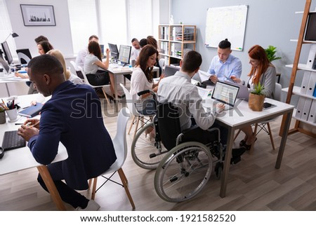 Side View Of A Disabled Businessman Sitting On Wheelchair Using Laptop Working In Office Royalty-Free Stock Photo #1921582520