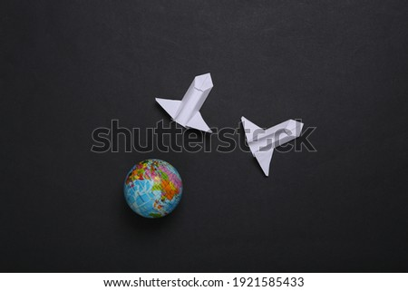 Origami space rocket shuttle and globe on black background. Space flight concept. Minimalism