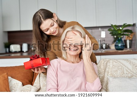 Cute teen child girl, kid daughter having fun covering mum eyes holding present red gift box making Mothers Day surprise greeting happy mom or grandmother on spring holiday at home. Royalty-Free Stock Photo #1921609994