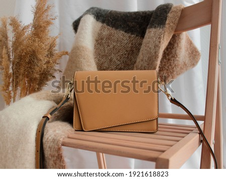 Beige trendy women's bag, against the background of a beige scarf accessory, lying on a chair. Photos for studios, showrooms, boutiques and shops selling women's accessories.