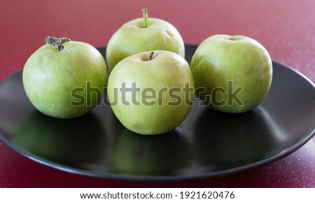 A few green fresh apples lie on a black platter on the red table. There is a free space for the inscription.