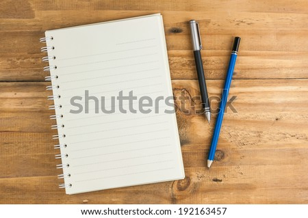 blank notebook with pen and pencil on wooden table, business concept Royalty-Free Stock Photo #192163457