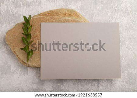 Gray paper business card, mockup with natural stone and boxwood branch on gray concrete background. Blank, flat lay, top view, still life, canvas, copy space.