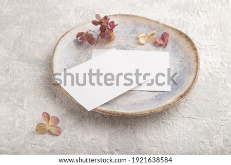 White paper invitation card, mockup with dried hydrangea flowers on ceramic plate and gray concrete background. Blank, side view, still life, copy space.
