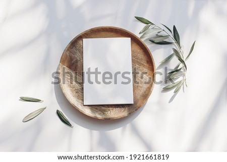 Summer wedding stationery mock-up scene. Blank greeting card, wooden plate, olive tree leaves and branches in sunlight. White table  background with palm shadows. Feminine flat lay, top view. Royalty-Free Stock Photo #1921661819