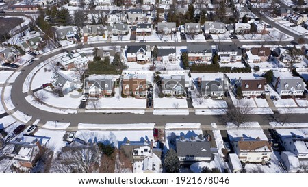 aerial drone camera shot over a suburb of Long Island, NY in the morning, after a snowfall. The houses are arranged neatly around a curved road. Royalty-Free Stock Photo #1921678046