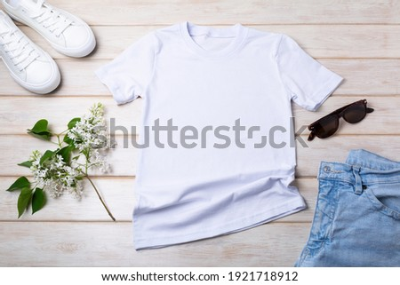White women's cotton T-shirt mockup with lilac, blue jeans, sport shoes and sunglasses. Design t shirt template, tee print presentation mock up Royalty-Free Stock Photo #1921718912