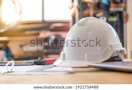 Construction concepts. White safety helmets blueprints on the engineering desks. Hard safety wear helmet hat on desks at construction site Royalty-Free Stock Photo #1921758488