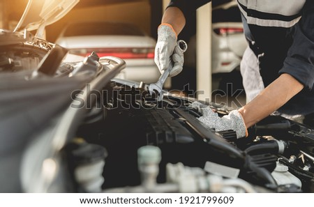 Automobile mechanic repairman hands repairing a car engine automotive workshop with a wrench, car service and maintenance,Repair service. Royalty-Free Stock Photo #1921799609