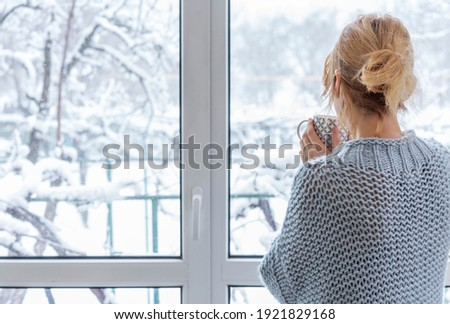 A woman looks out of the window at the snow-covered outdoors