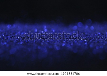 Wallpaper phone shining glitter.Glitter radiance surface.  blue glitter with shining bokeh on a black background.Festive bright background. New Year and Christmas background. Shining texture Royalty-Free Stock Photo #1921861706