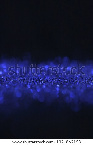 Wallpaper phone shining glitter.Glitter radiance surface.  blue glitter with shining bokeh on a black background.Festive bright background.  Royalty-Free Stock Photo #1921862153