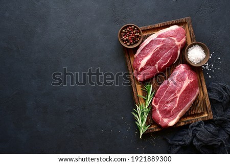 Raw organic marbled beef steaks with spices  on a wooden cutting board on a  black slate, stone or concrete background. Top view with copy space. Royalty-Free Stock Photo #1921889300