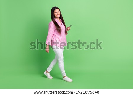 Full length body size view of attractive cheerful girl going using gadget blogging app smm isolated over green pastel color background
