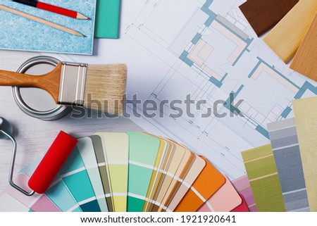 Painter and decorator work table with house project, color swatches, painting roller and brush, top view Royalty-Free Stock Photo #1921920641
