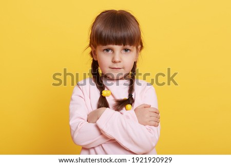 Beautiful little girl standing against yellow background, being offended, keeping arms folded, waiting for explanation, female child with two pigtails, attractive kid. Royalty-Free Stock Photo #1921920929