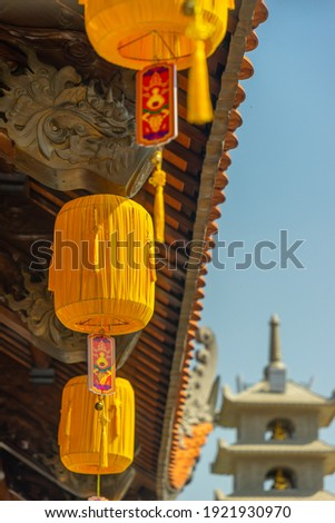 Beautiful traditional yellow silk lanterns are are hanging on the roof of the temple at Vinh Nghiem monastery in Ho Chi Minh city, Vietnam. Religion concept. Royalty-Free Stock Photo #1921930970