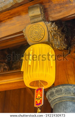 Beautiful traditional yellow silk lanterns are are hanging on the roof of the temple at Vinh Nghiem monastery in Ho Chi Minh city, Vietnam. Religion concept. Royalty-Free Stock Photo #1921930973