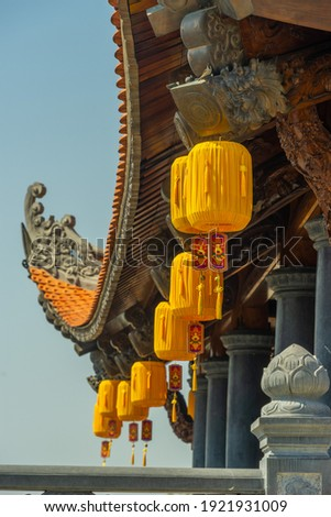 Beautiful traditional yellow silk lanterns are are hanging on the roof of the temple at Vinh Nghiem monastery in Ho Chi Minh city, Vietnam. Religion concept. Royalty-Free Stock Photo #1921931009