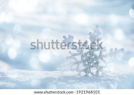 Beautiful decorative snowflake on white snow. Space for text