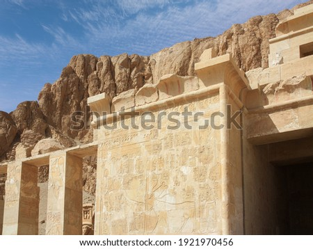 A section of an outer wall at the temple of the Egyptian Queen Hatshepsut in Egypt. There are hieroglyphs and pictures on the wall. In the background the mountains with blue sky and clouds.