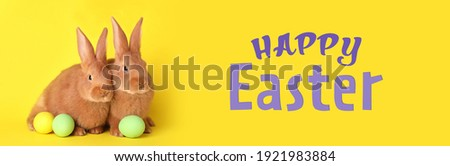 Happy Easter! Cute bunnies and dyed eggs on yellow background, banner design Royalty-Free Stock Photo #1921983884