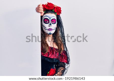 Young woman wearing day of the dead custome holding blank empty banner relaxed with serious expression on face. simple and natural looking at the camera.