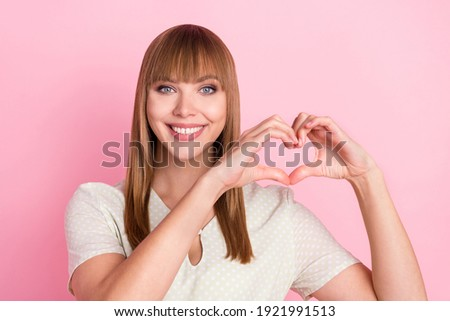 Portrait of attractive cheerful girl showing heart symbol together forever isolated over pink pastel color background