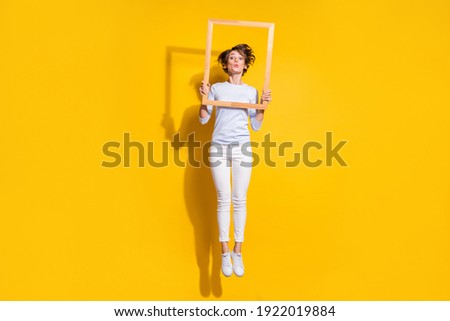 Photo of crazy lady jump send air kiss hold wooden frame wear white shirt trousers footwear isolated yellow color background