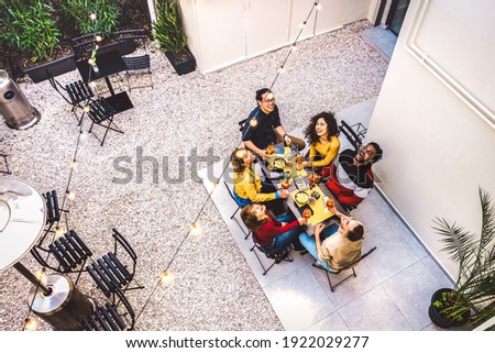 High angle top view of happy friends drinking cocktails and having fun at restaurant garden party - Food and beverage  concept with young people together at home patio - Dark warm filter