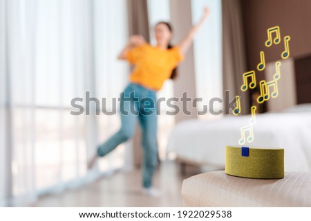 A portable smart yellow speaker plays music. Signs of melody. In the background, a woman dances in a blur. The concept of modern gadgets and entertaiment.