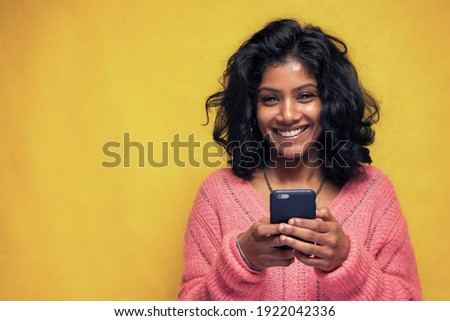 Beautiful Sri Lanka girl makes technology poses with yellow bright background - Young woman uses mobile phone to chatting and messaging Royalty-Free Stock Photo #1922042336