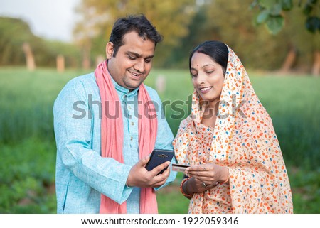 Happy indian rural farmer couple using smartphone to make online payment with debit card in agricultural field, shopping on internet with cellphone secure banking service system concept. Royalty-Free Stock Photo #1922059346