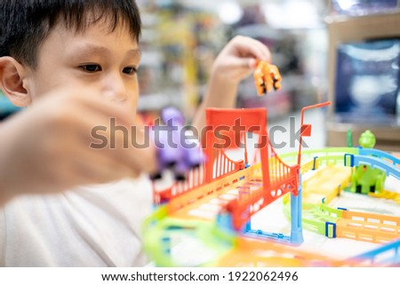 Happy kindergarten kid boy playing with rail road toy game,asian little child having fun enjoy with toys car in nursery,educational toys for children,leisure activity,education development concept