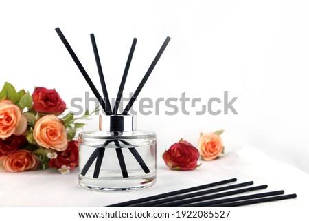 ชื่อผลงาน: luxury aroma scent reed diffuser glass bottle is on the white table with roses flowers to creat romantic and relax ambient in the bedroom with white cement wall background on the happy vale Royalty-Free Stock Photo #1922085527