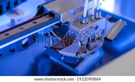 Three dimensional printing machine printing 3D plastic model at modern technology exhibition, factory - close up. Additive manufacturing, robotic automation technology concept Royalty-Free Stock Photo #1922090864