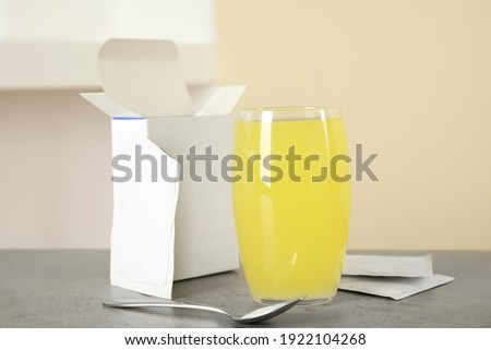Glass with dissolved drug, medicine sachets and spoon on grey table