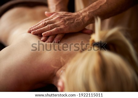 Fragment photo of a blonde lady with bare back getting a massage by professional masseur