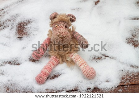 Knitted from yarn sheep on white snow in winter.